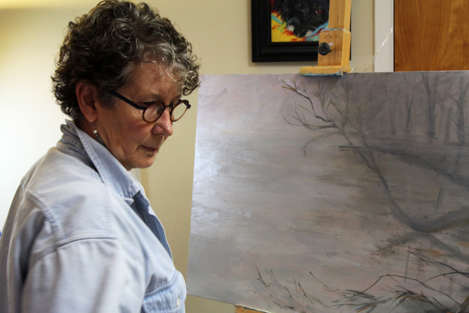 Fine Artist, Phyllis Sharpe, painting a waterscape in oil, in her studio