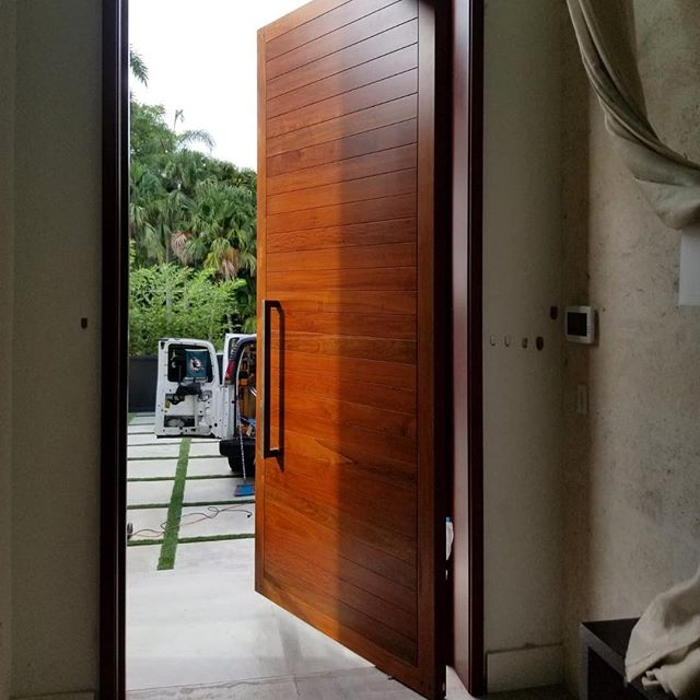 """Hand made and hand finished solid #Ipe wood pivot front door with reinforced steel. 11'H x 5'W x 3""""T and weighing in at over 800lbs. Using @fritsjurgens concealed pivot hinges. Manufactured and installed by #byblosgroup"""