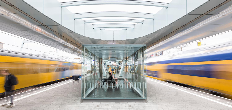 Reiziger wachtend tussen rijdende treinen in een symmetrisch beeld in het nieuwe station Arnhem, geopend op 19 november 2015