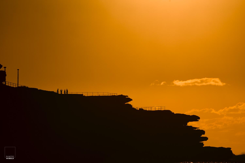 Silhouetten van mensen die aan yoga doen bij zonsopgang in Bondi Beach, Sydney, Australië