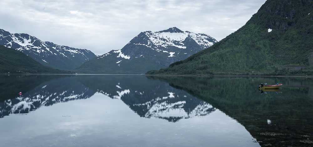 A boat in a Norwegian fjord with mountains reflecting off water.