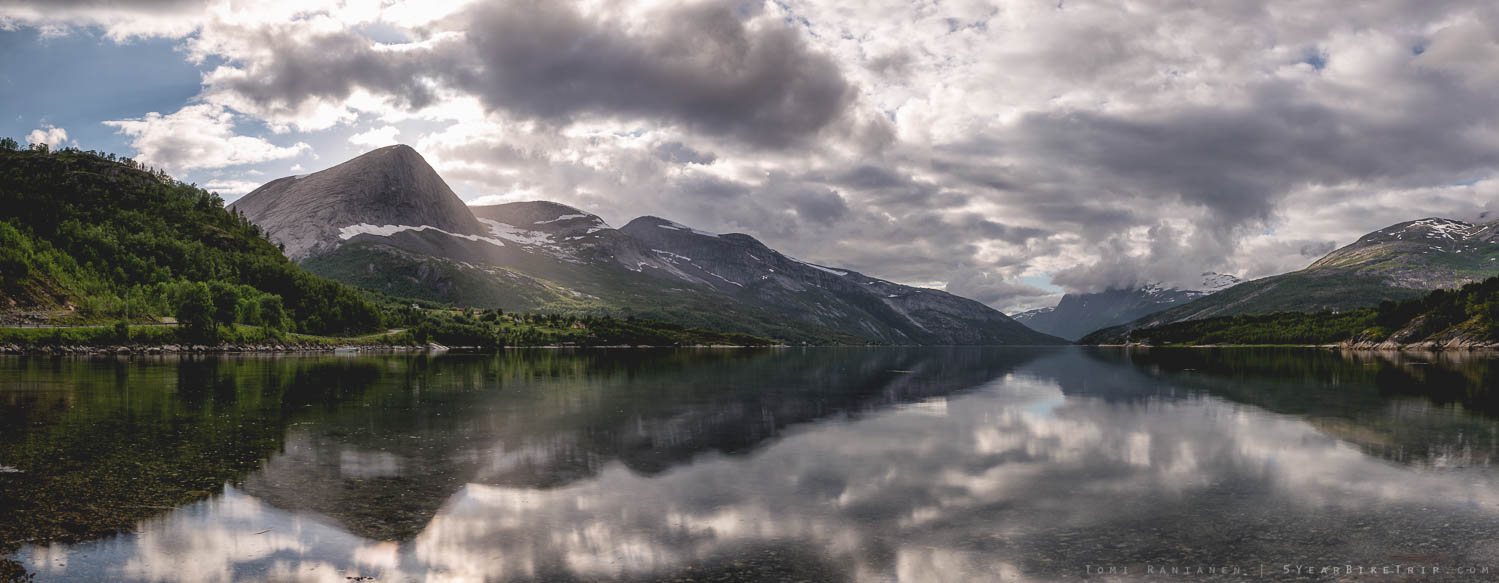 Mountains and clouds reflecting off the fjord.