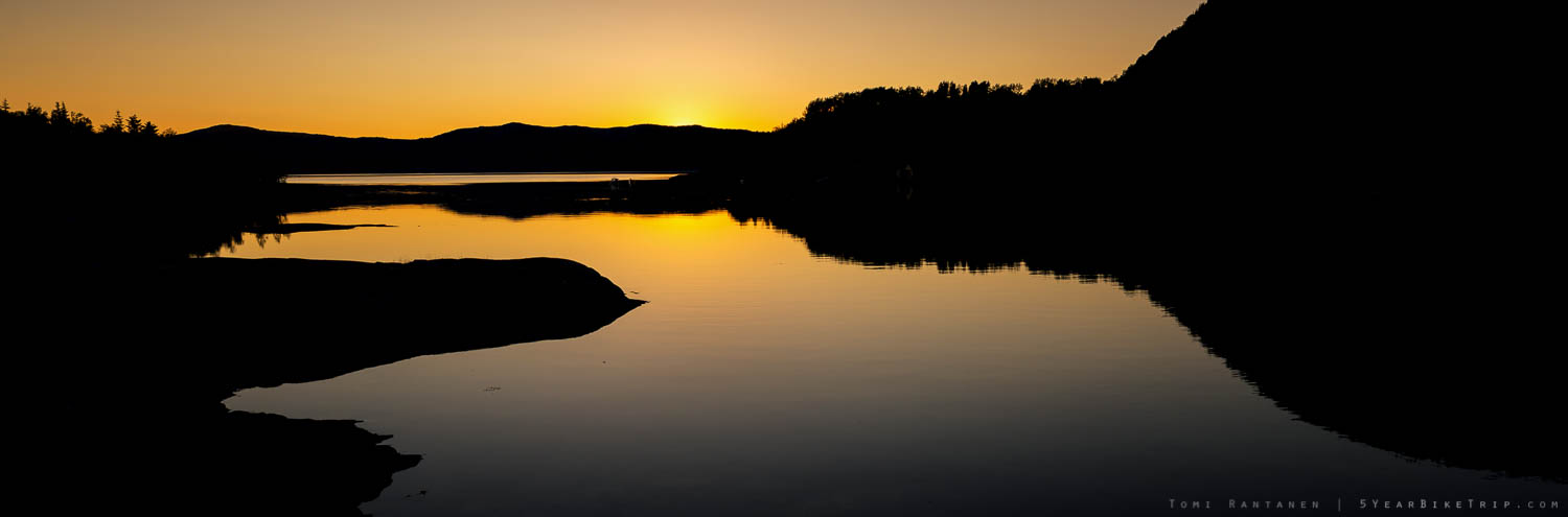 Sky reflecting off water with a silhouette landscape after sunset.