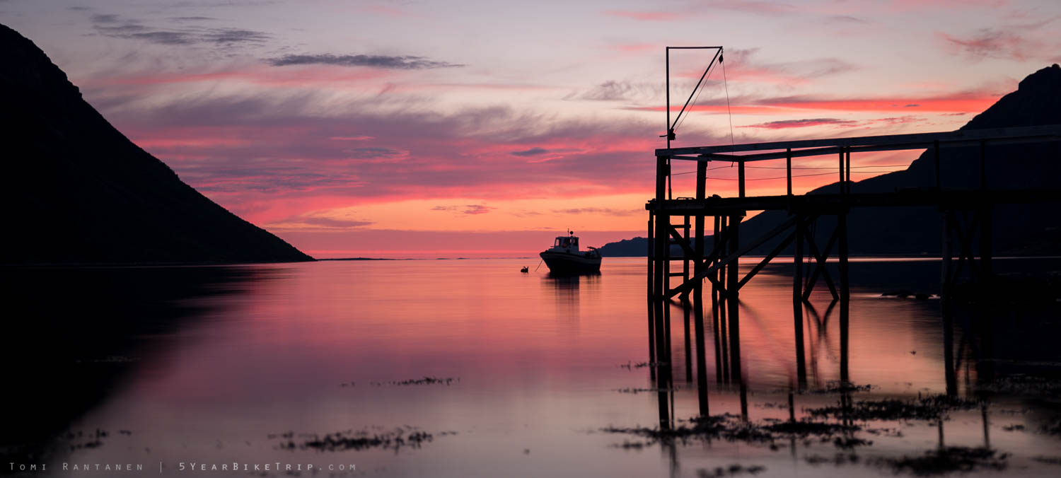 Fishing boat by a pier at sunset in Norway.