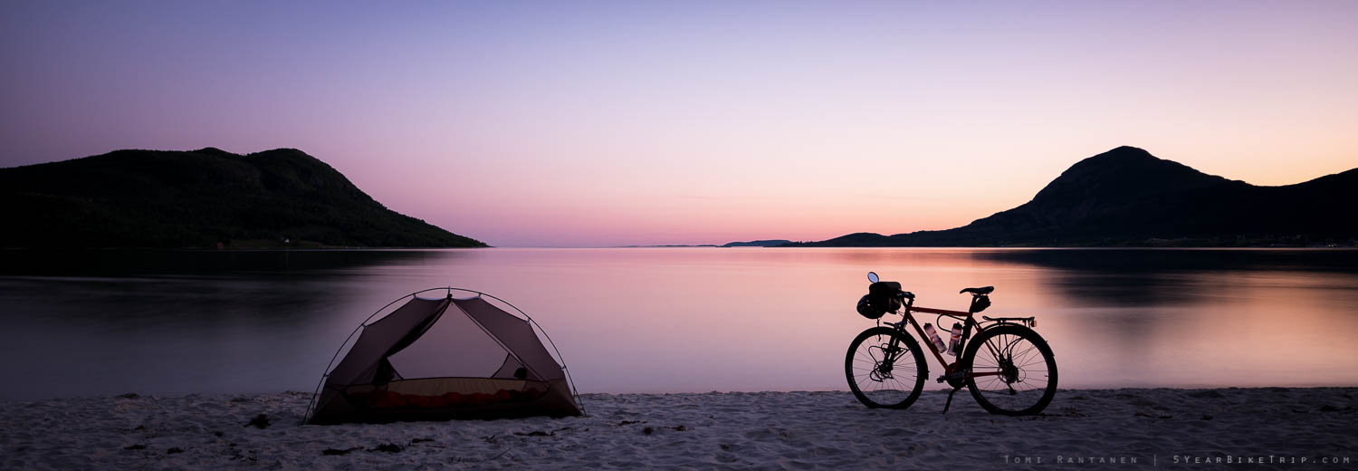 Tent and bike silhouetted on a beach after sunset.