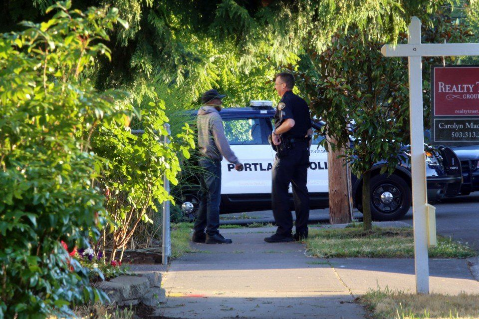 Police respond to a fatal shooting early Thursday in Southeast Portland. Investigators say a resident fatally shot an intruder. A police officer talks to a neighbor across the street from the home where the intruder was shot. (Rebeca Bagdocimo/Staff)