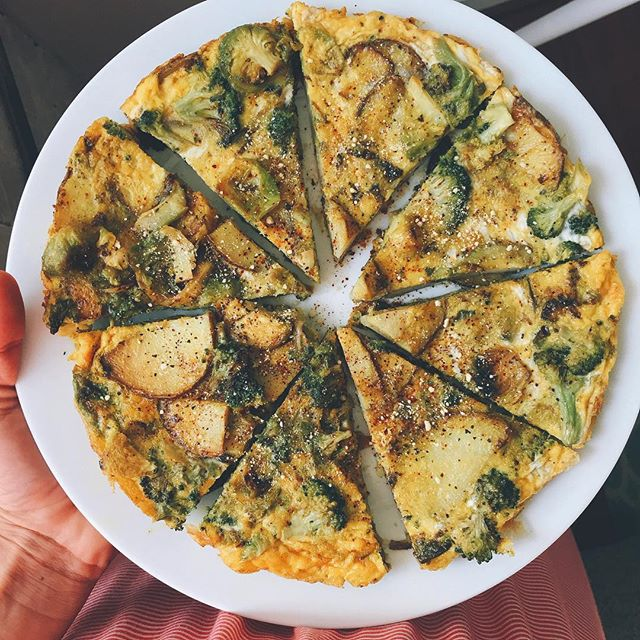 when i used to live in spain for a while w/ different families this is what i ate pretty much every single day- for morning breakfast; Spanish omelette. 🤤 - when i was out over the weekend i ordered one and forgot how much i loved them. super easy to make, last's up to a week & you can either have it cold or warm it back up (i prefer cold) for on the go, or fast dinner 👌🏻 👇🏼 . . less than 30 mins serves 2-3. 👉🏼 in your cast iron pan add 1-2 tbsp olive oil to medium heat. Thinly slice up a russet potato (can use sweet potatoes but not the same); add to cast iron w/ sea salt pepper & any other seasonings. Sauté for about 10 or so mins until the potatoes begin to brown & crisp. In a large bowl add your eggs (i used 6). Whisk. (I also added in extra leftover pre cooked veggies, but these are mainly just done with onions). Turn down the heat to low/ medium add in your eggs to the cast iron and make sure it is evenly spread. Allow to cook for about 10 mins. You can always throw it under the broiler on high for the remaining five mins to make sure the top cooks evenly OR carefully flip it to cook the other side. As long as the eggs are all the way cooked you're good! Lasts up to week in fridge or can be left out. 🖤 #eggs #breakfastonthego #spanishomlette