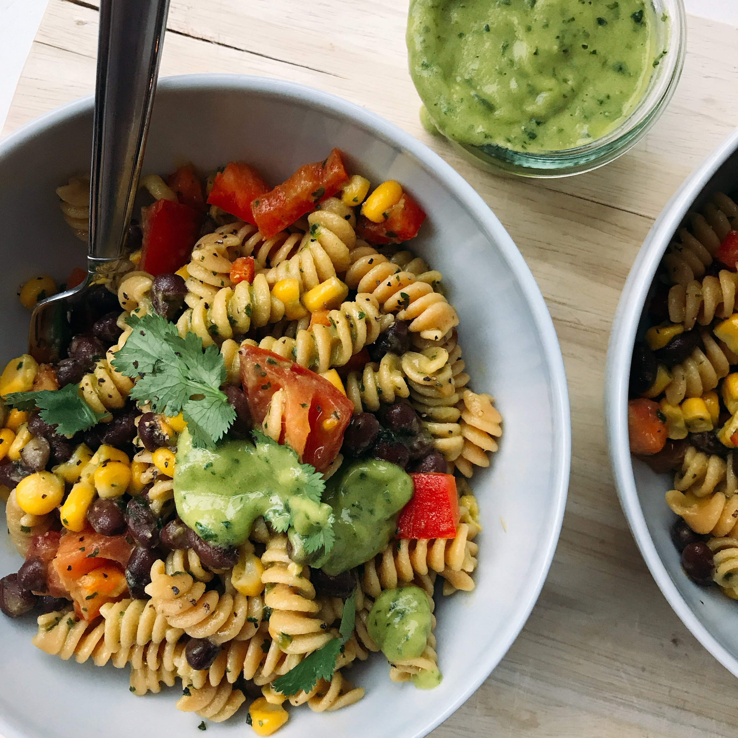 A delicious plant-based Mexican chickpea pasta salad packed with black beans, cherry tomatoes, corn, red peppers tossed in a creamy and light cilantro avocado sauce!