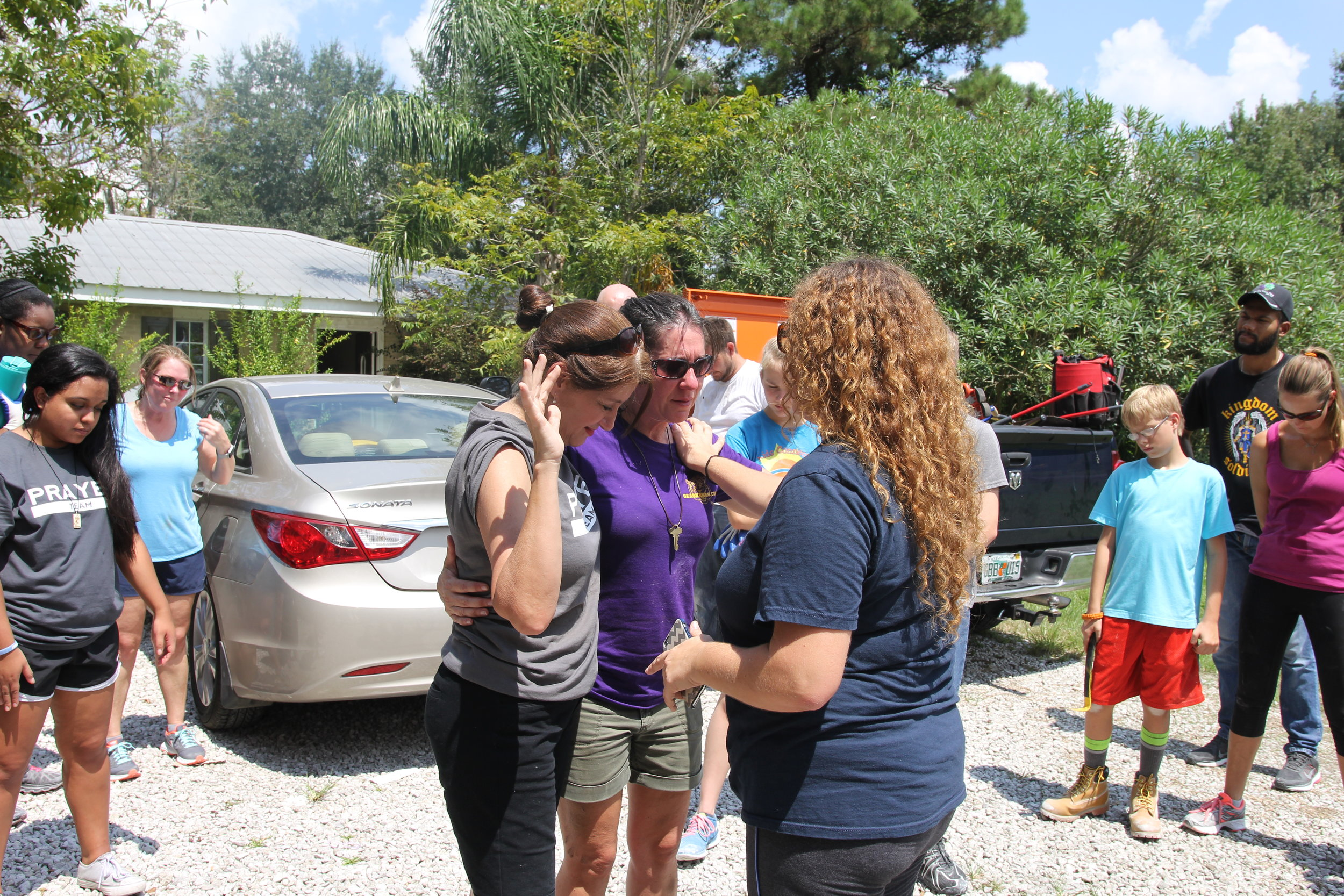 Heather Allan, Highpoint Church Team Leader praying with Kim Sandras (Tuscaloosa, Al team leader) for a family affected by the flood.