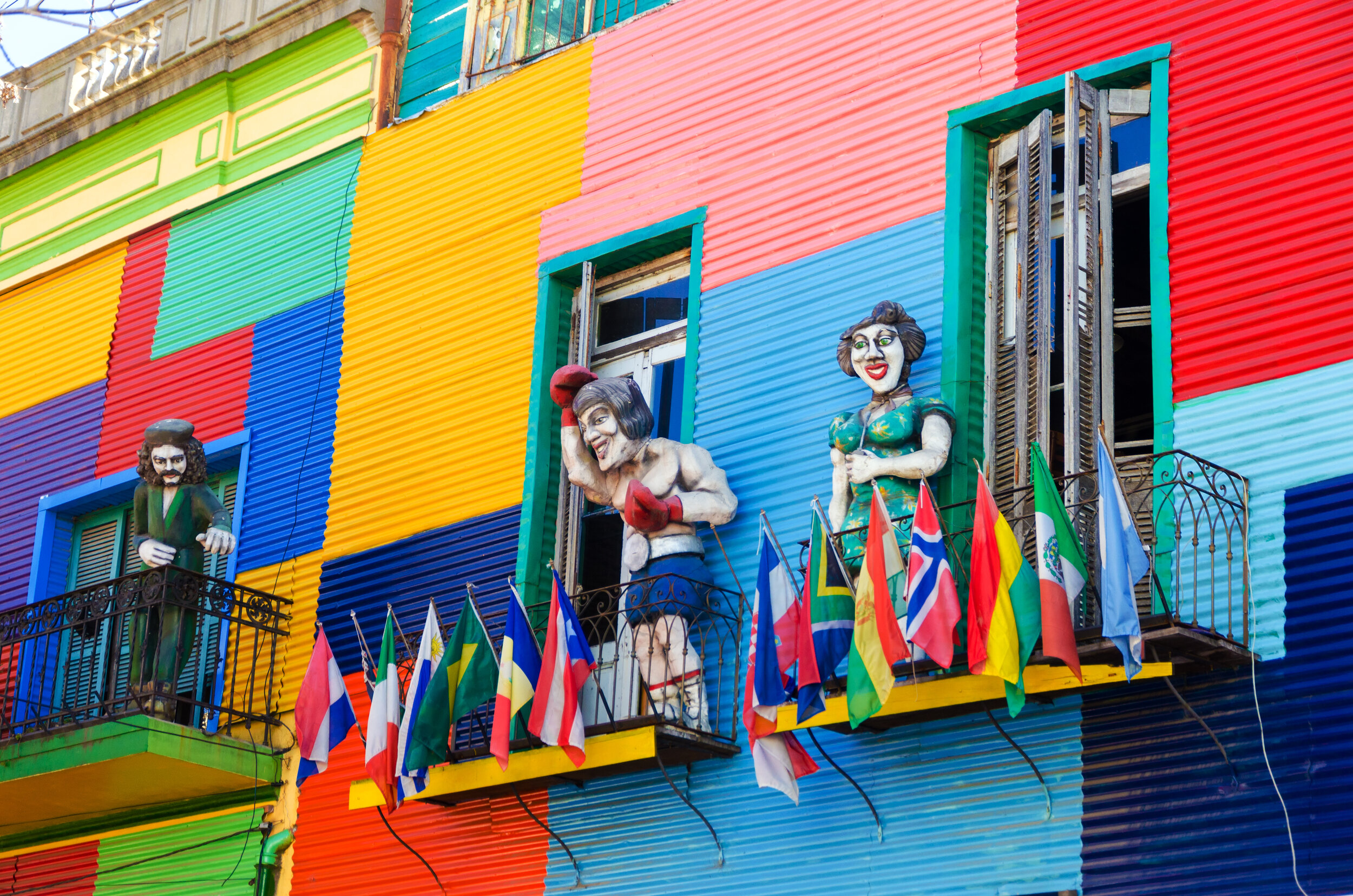 A colorful building in La Boca neighborhood of Buenos Aires with statues and flags.jpg