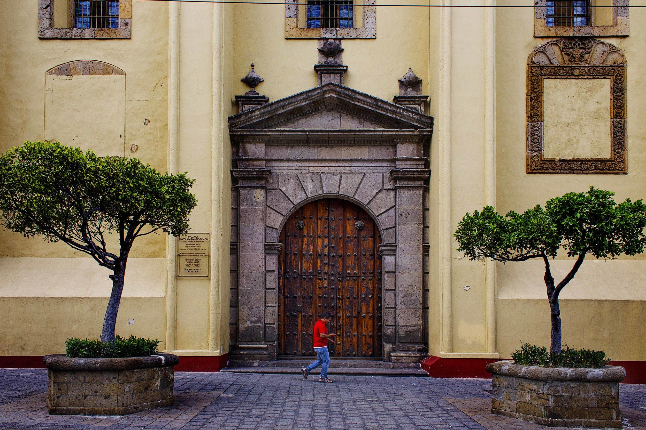 Day 70 - Guadalajara, Jalisco, Mexico   Man texting while walking in front of theTemplo de Santa María de Gracia.