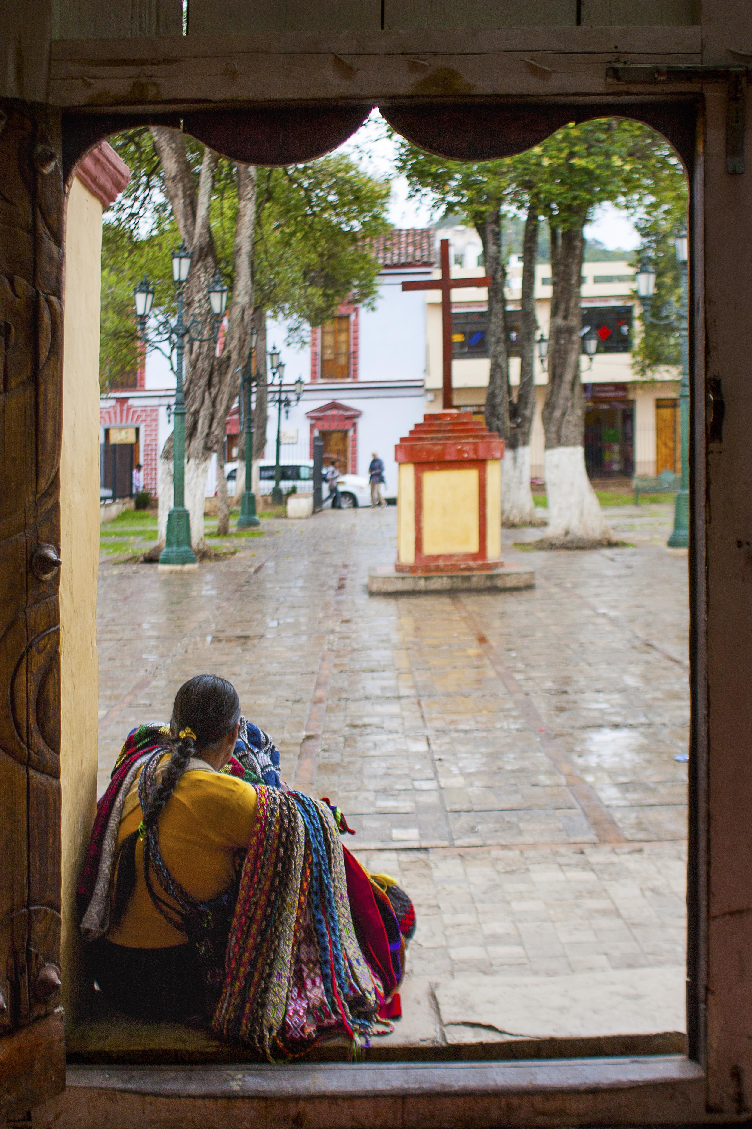 Day 127 - San Cristobal de las Casas, Chiapas, Mexico   We take a day off from tours and walk around the cobbled streets of San Cristobal to take it all in. It happened to rain so the usual hustle of the streets was missing. Here, a lady waits for the rain to stop at the steps of a church so she can go back to selling her crafts.