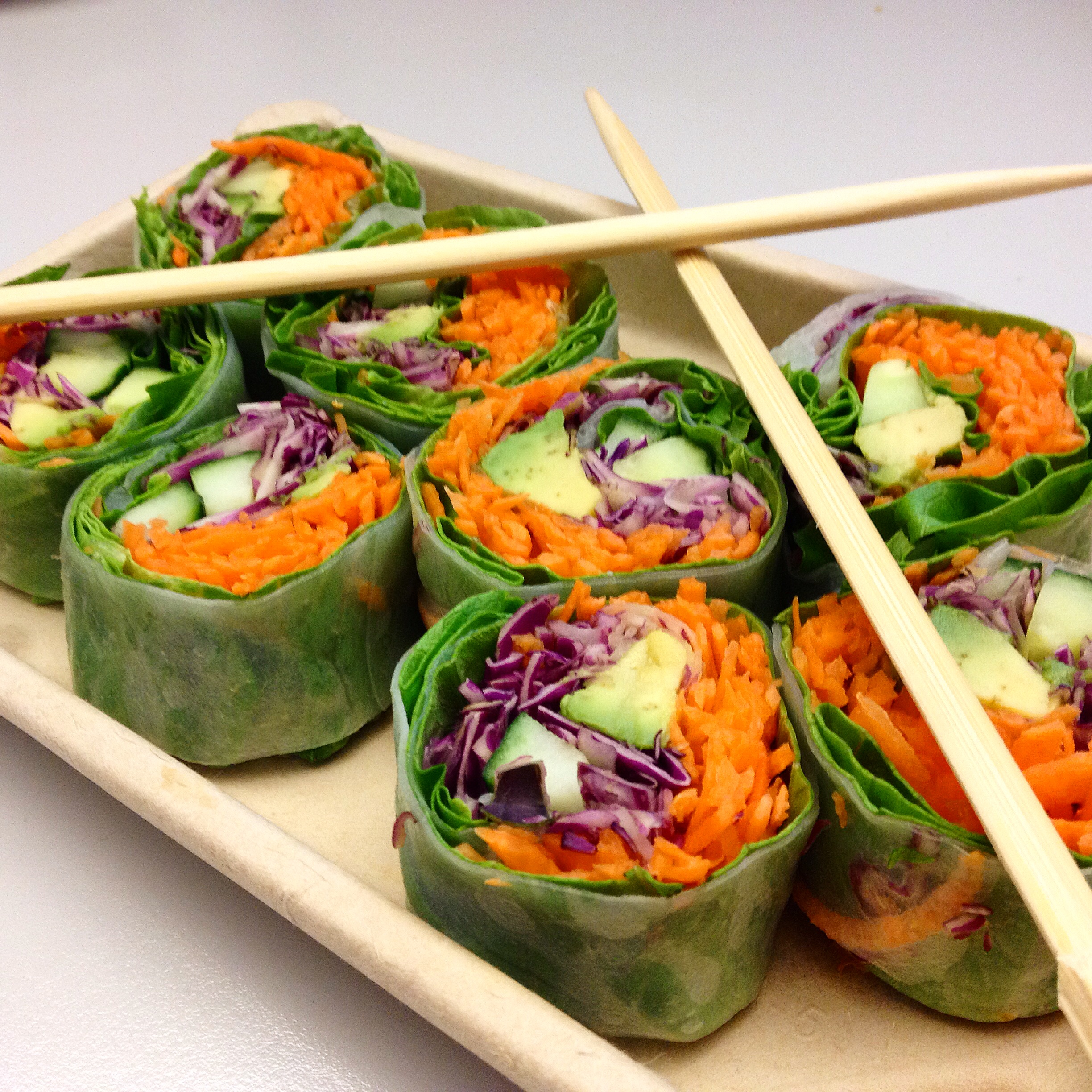 Veggie rolls made of spinach wrap, cabbage, carrots, avocado, cucumber. Place on wrap, roll, slice.