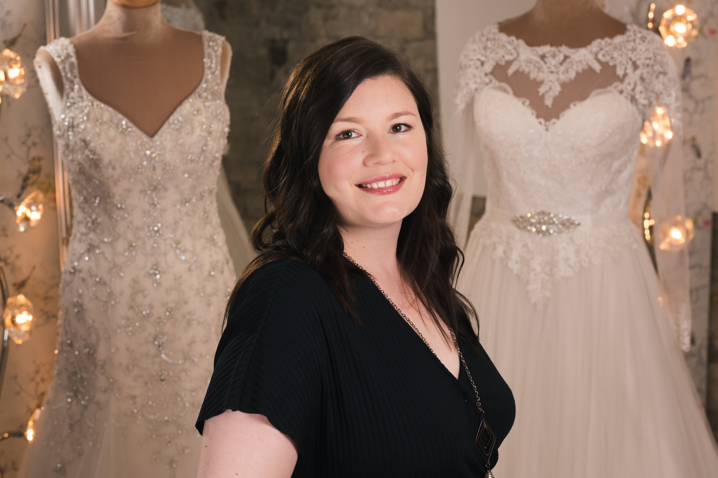 Picture of Louise at her bridal shop, Louise Perry Bridal.  Showing wedding dresses in the background.