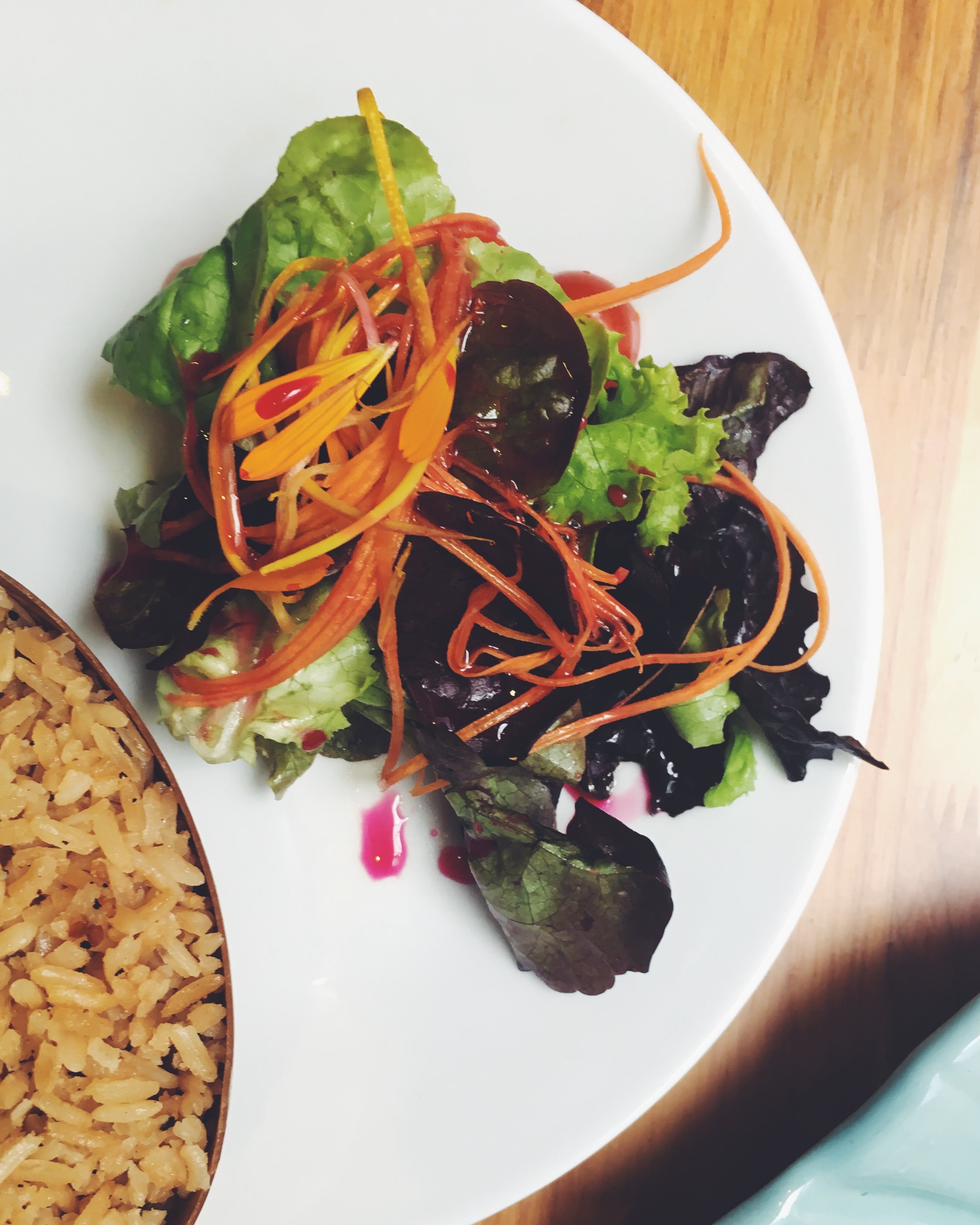 Side of greens and calendula with tropical dressing and coconut rice served in a coconut