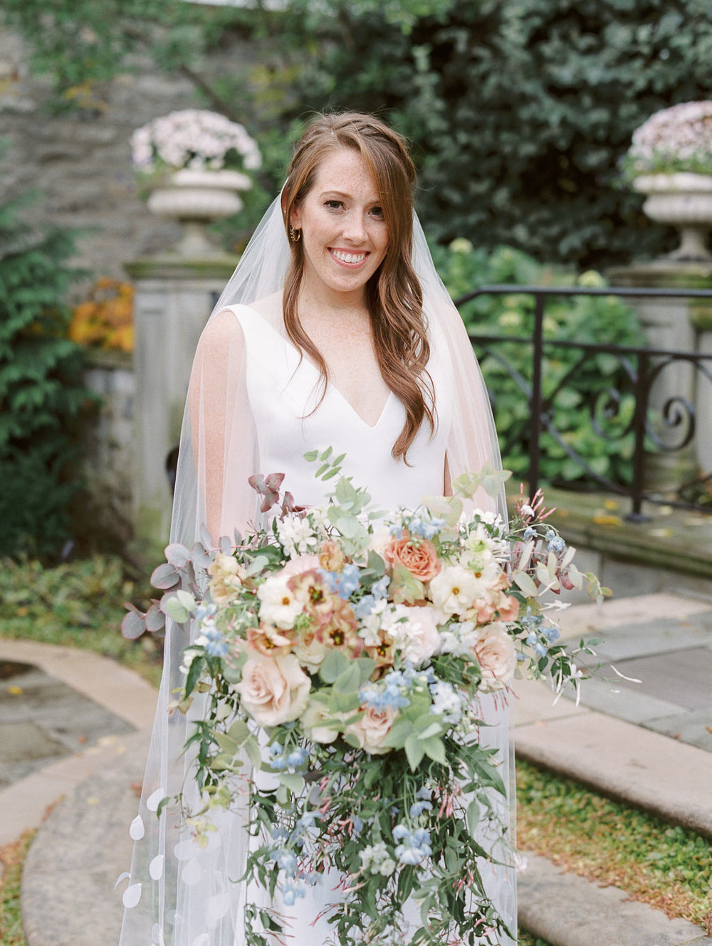 bride holding large garden bouquet in B Loved Bridal gown at Franklin Park Conservatory