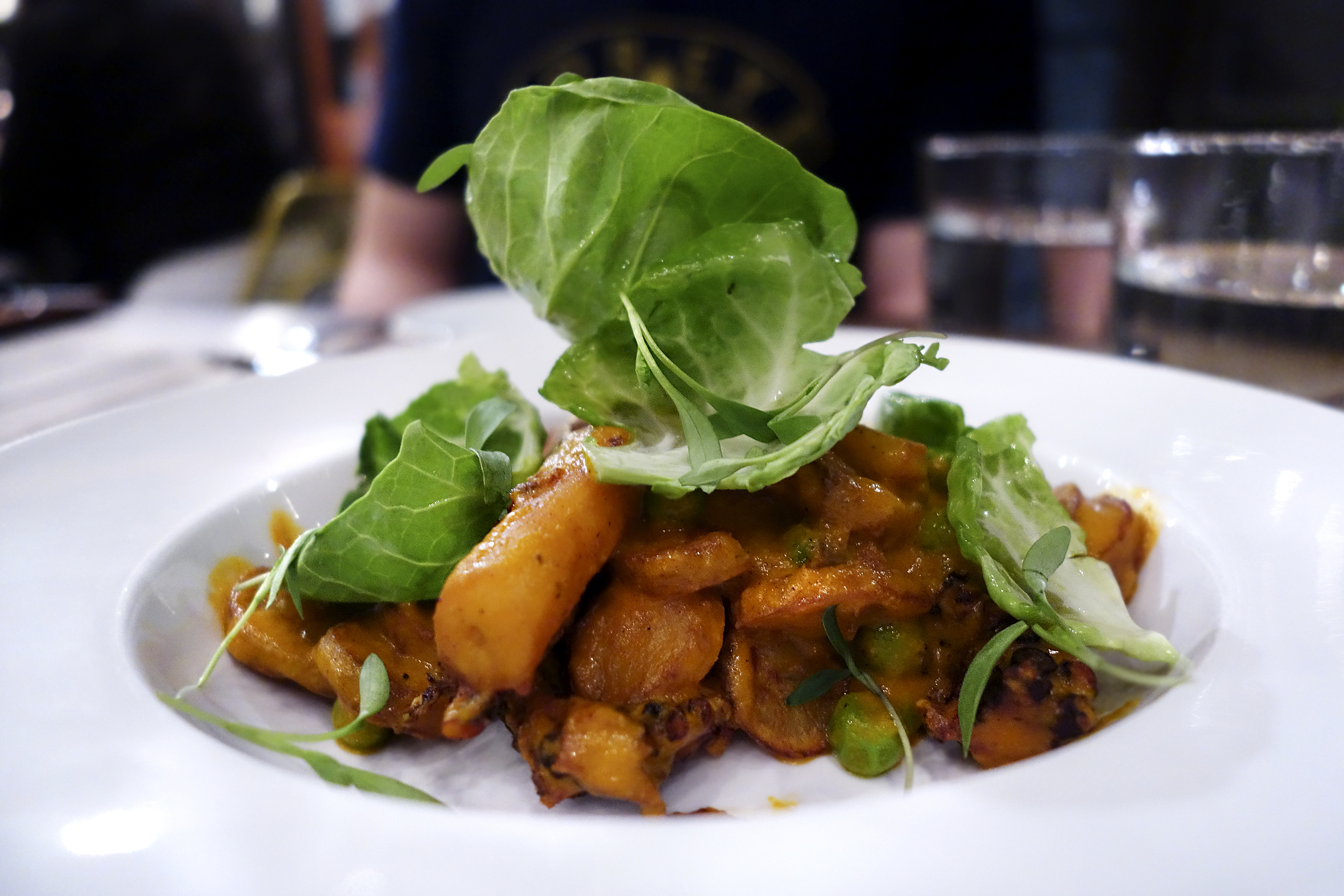 Indian Butter Octopus -  fingerling potato, english peas, brussels sprout leaves, cashews, cilantro ginger vinaigrette