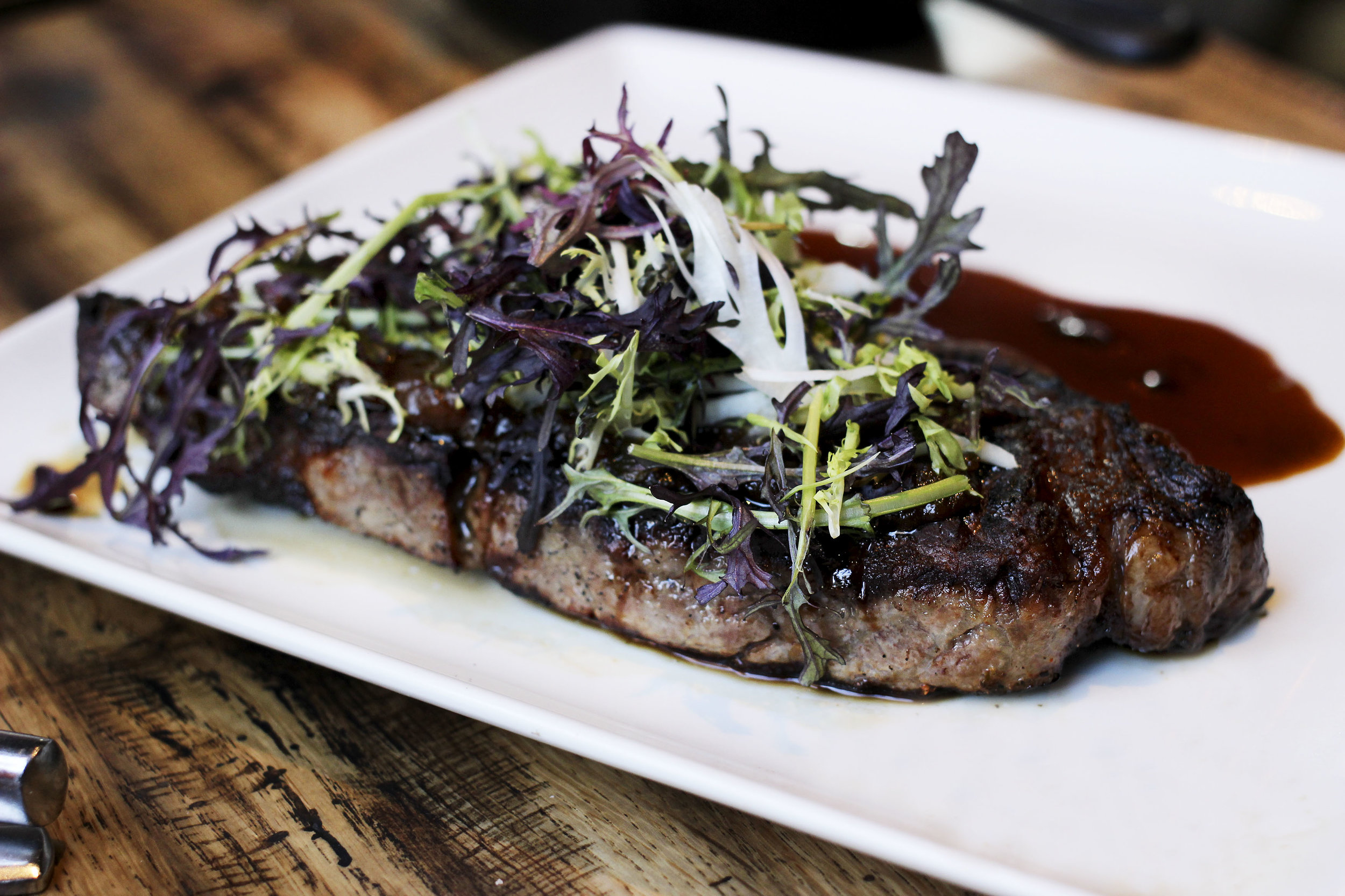 Prime NY Strip - 14 oz, charred onion-thyme jam, green peppercorn-cognac jus. Cooked Medium Rare.