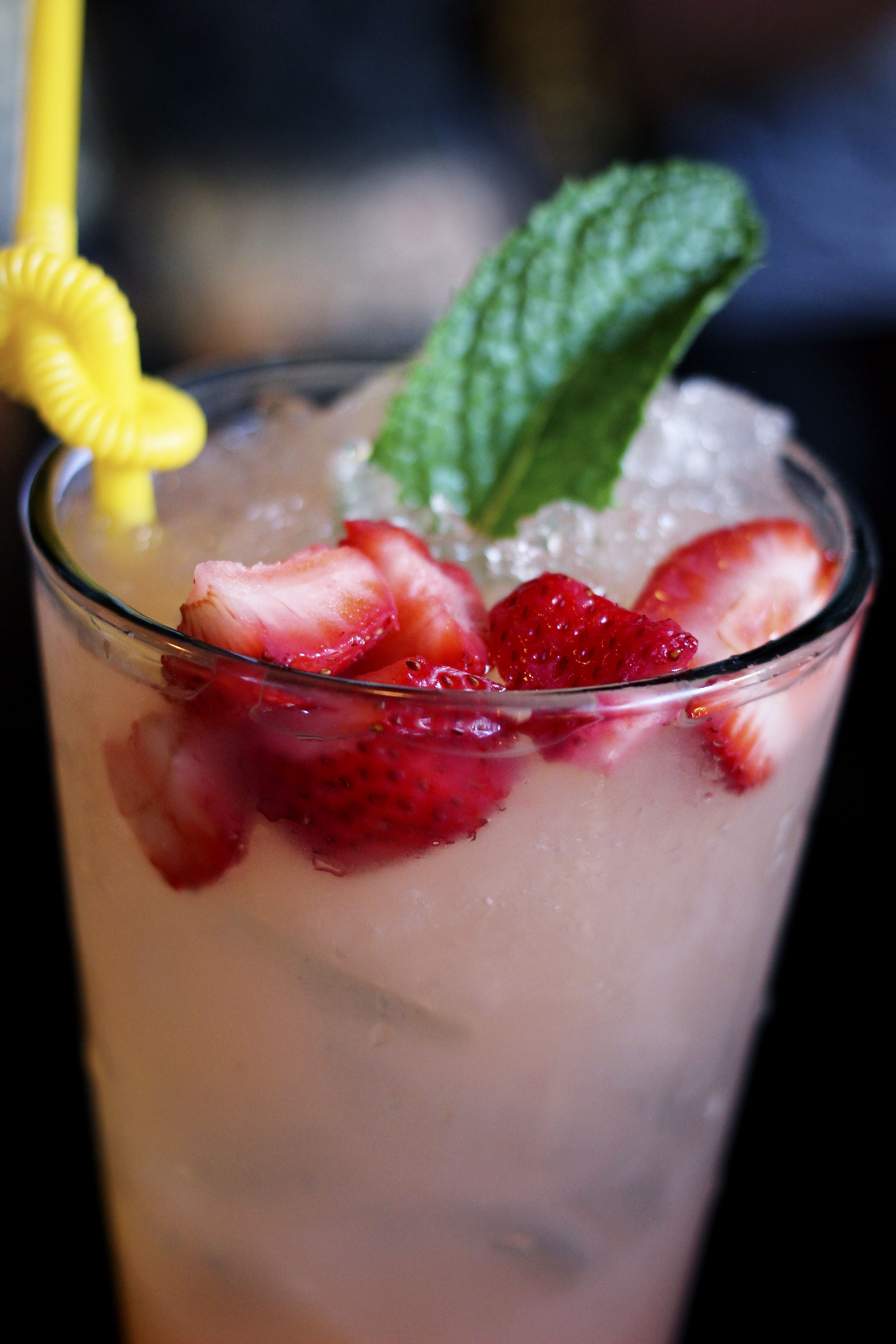 Tall glass of strawberry lemonade.