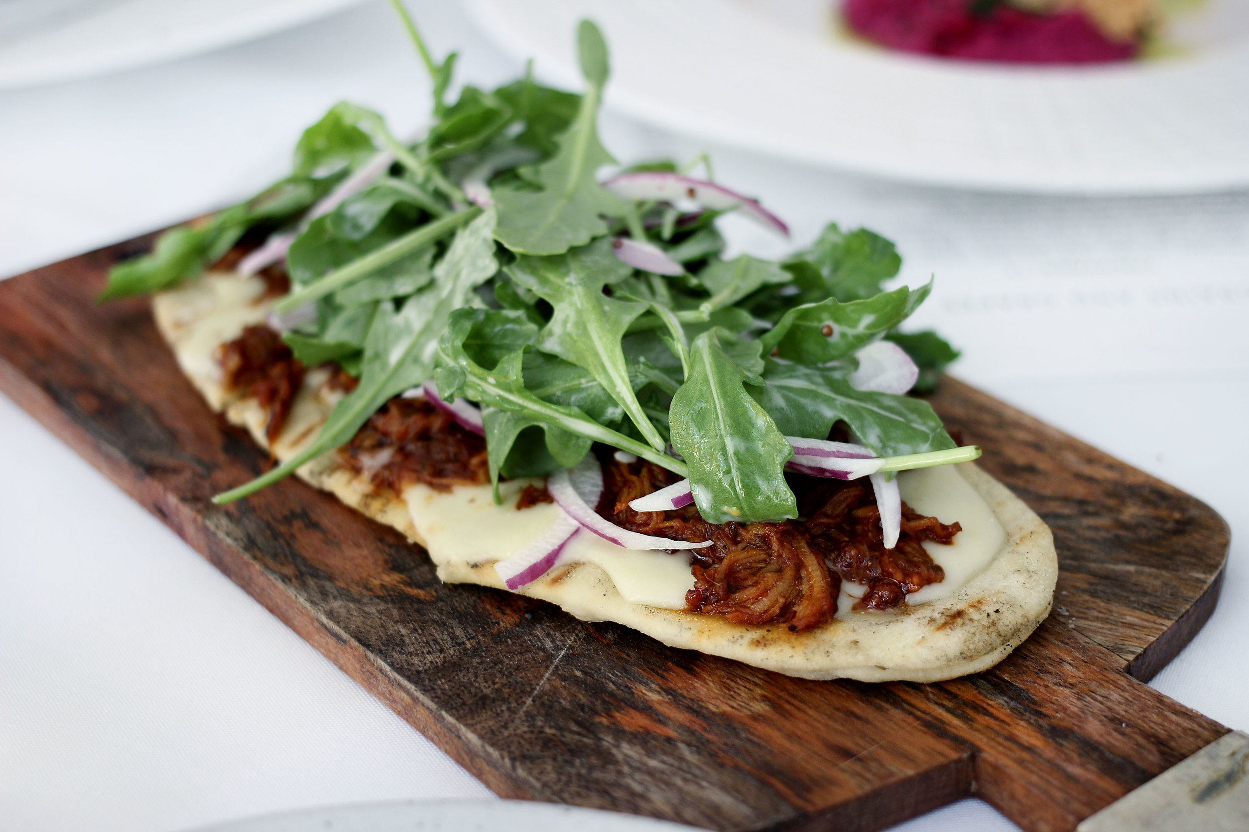 BBQ Flat Bread - Grilled Flatbread, smoky barbeque pulled pork, white cheddar, arugula and red onions.