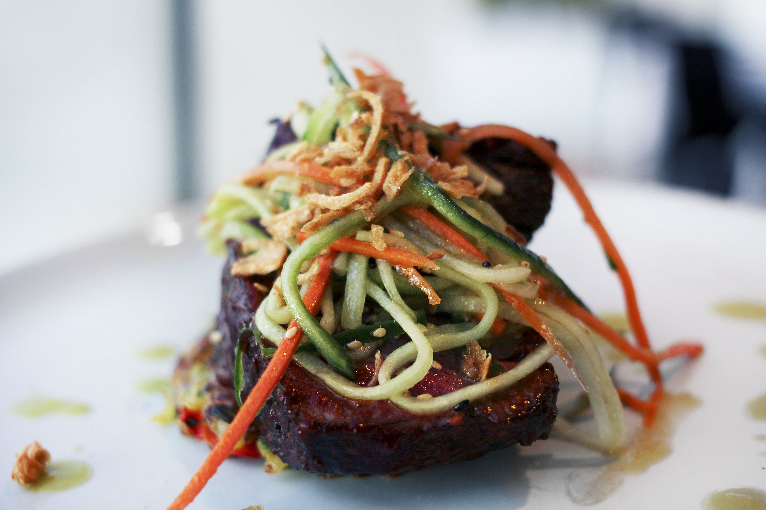 PRIME FILET OF BEEF - potato pancake, spicy sweet glaze, crispy onion, pickled vegetables.