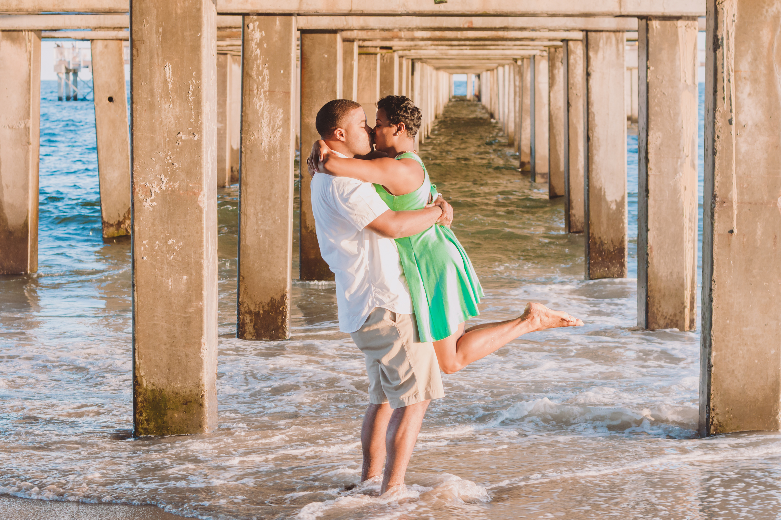 groom lifting bride during fun e session in coney island