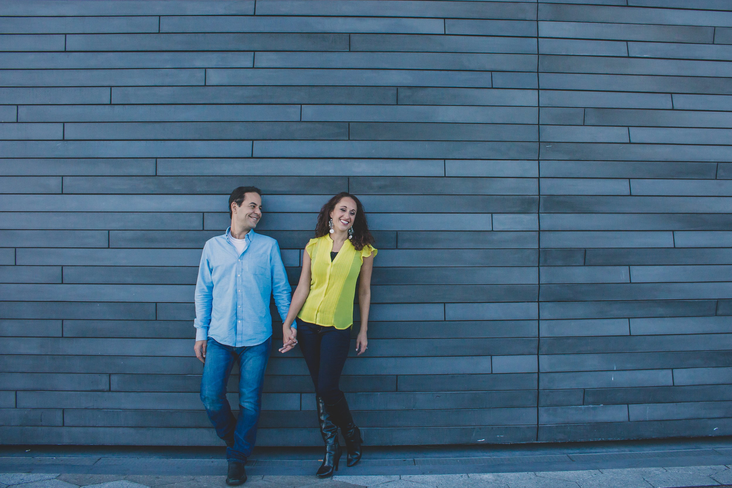 couple smiling holding hands in front of cool wall