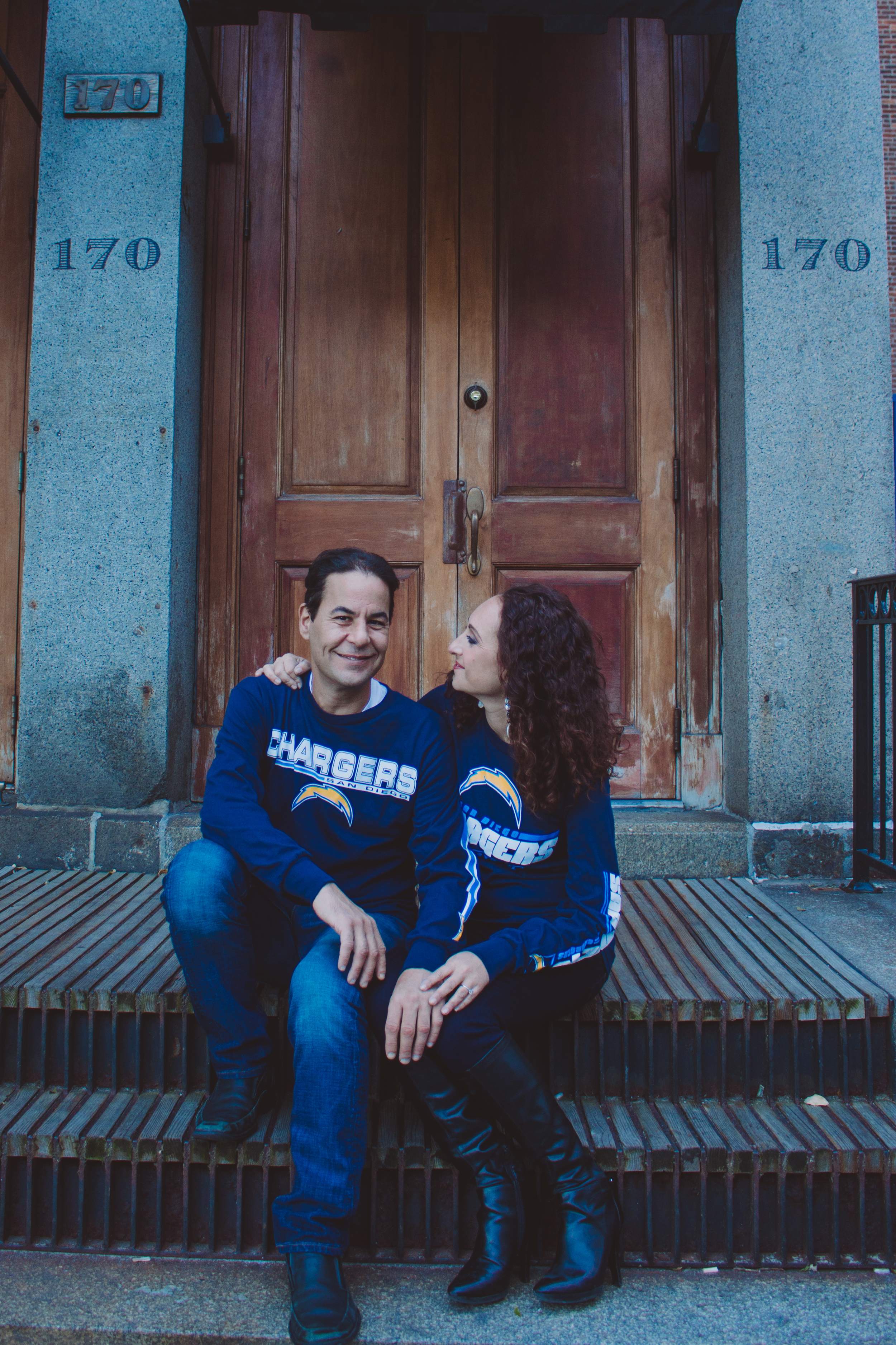 couple sitting on stairs in chargers sweaters