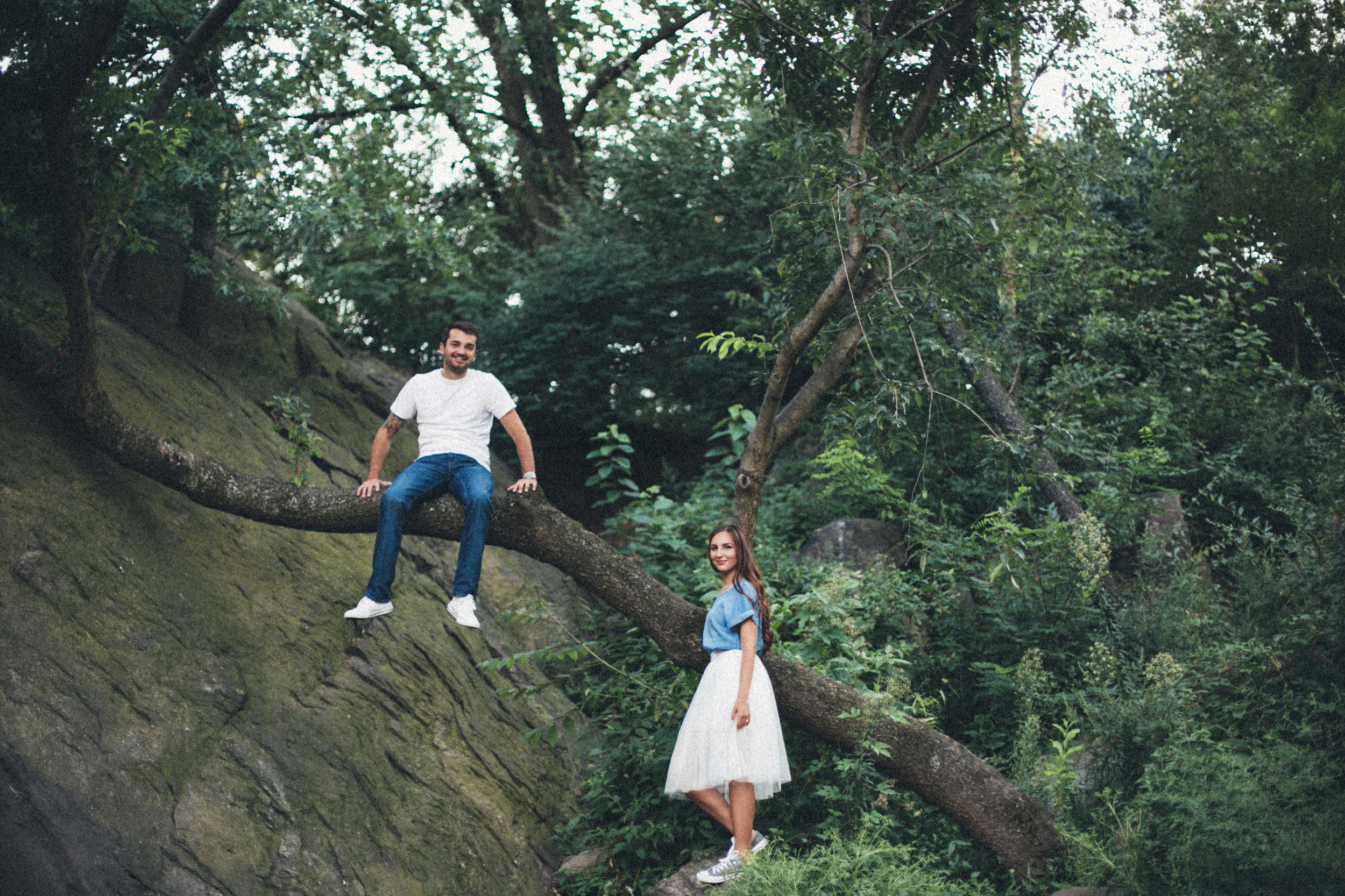 fun engagement session couple climbing trees in park