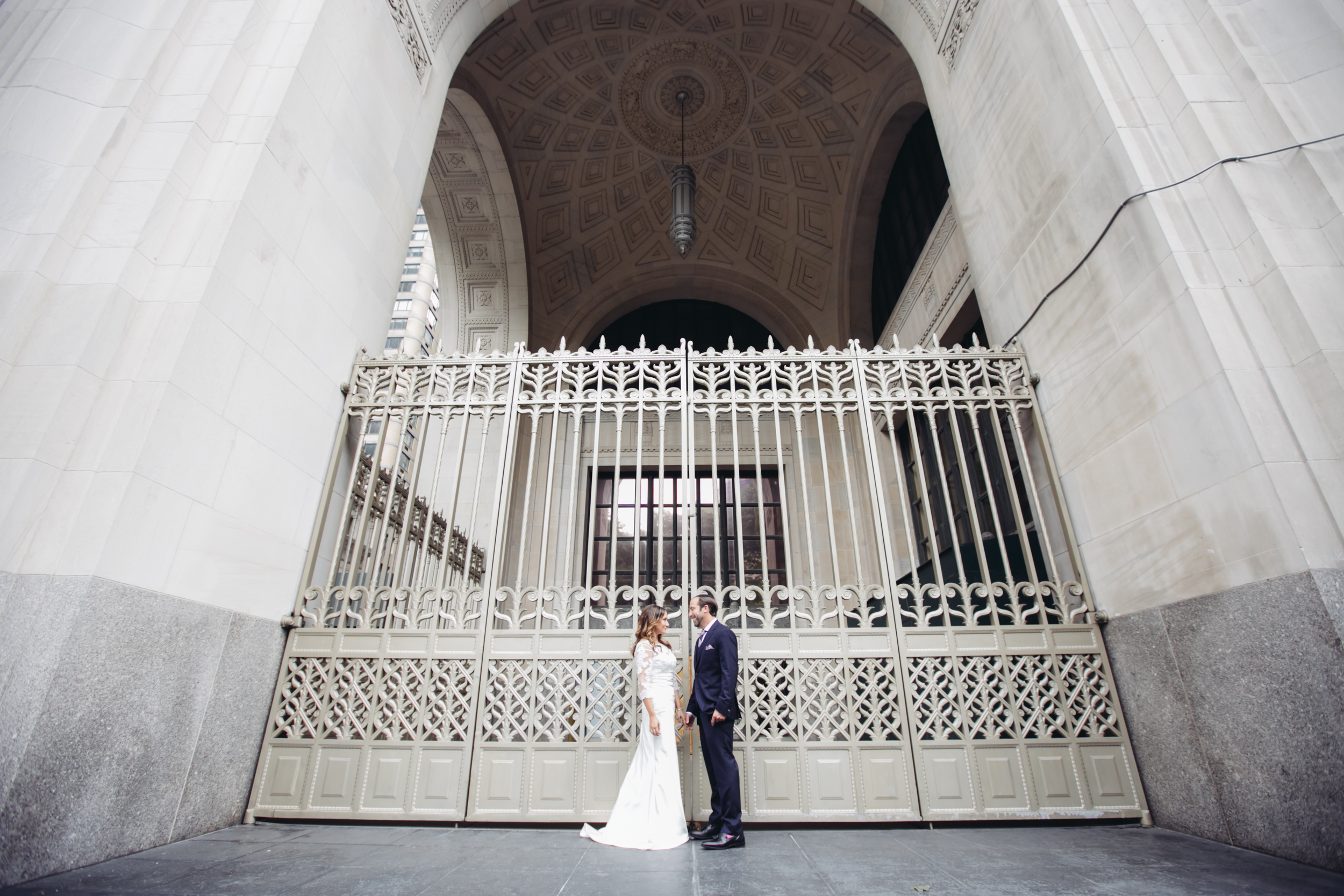 bride and groom in front of gate