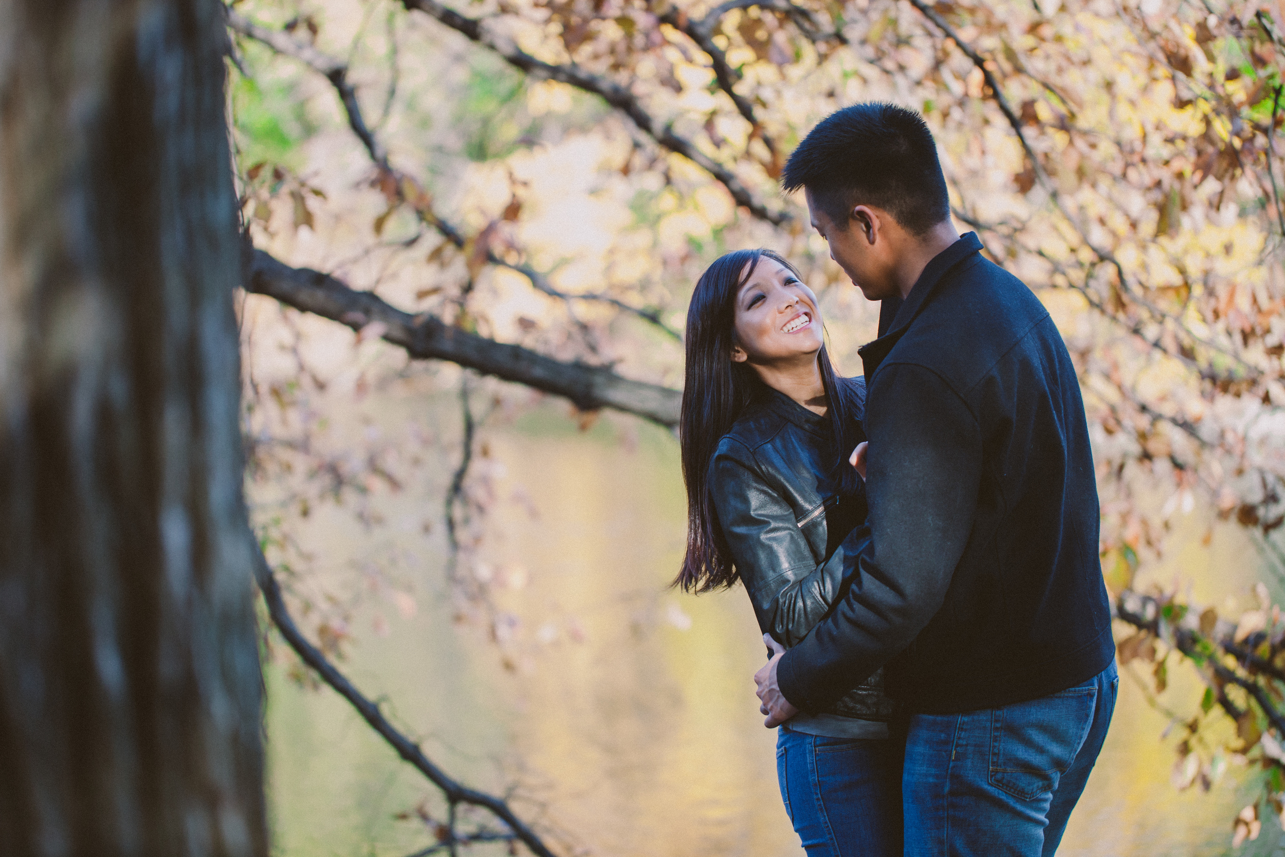 couple poses next to tree during autumn nyc engagement photoshoot