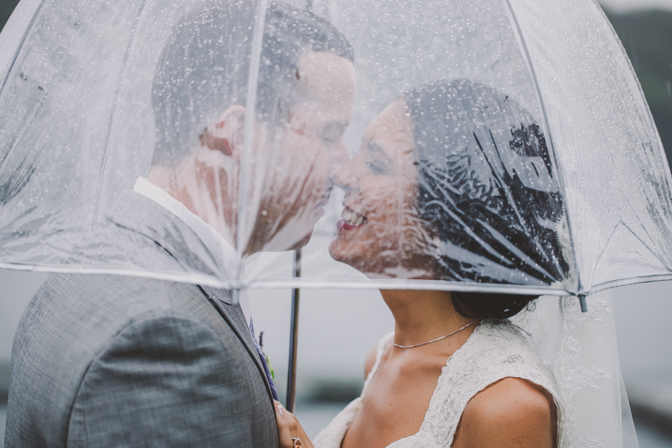 bride and groom under umbrella on a rainy wedding day