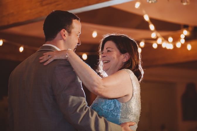 mother son dance under christmas lights at farm wedding