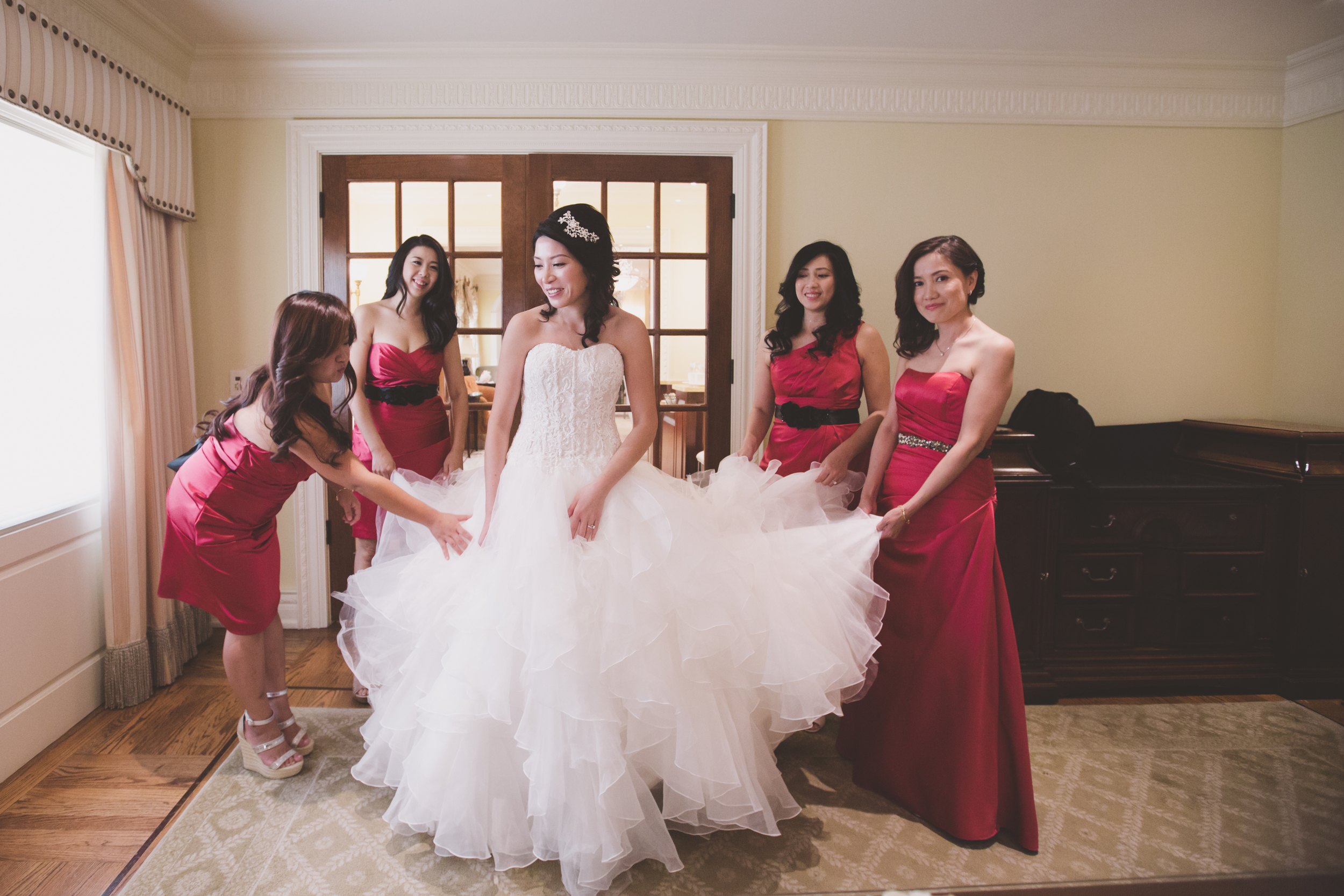 bride and bridesmaid getting the dress on