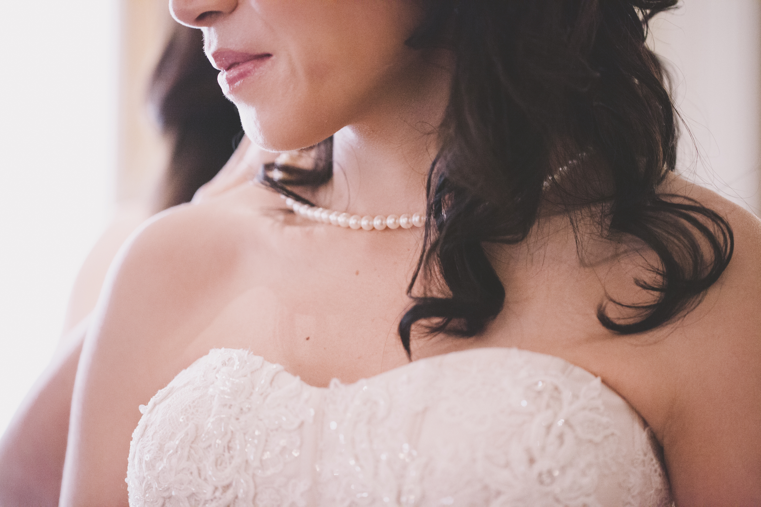 close up pearl necklace in wedding dress bride