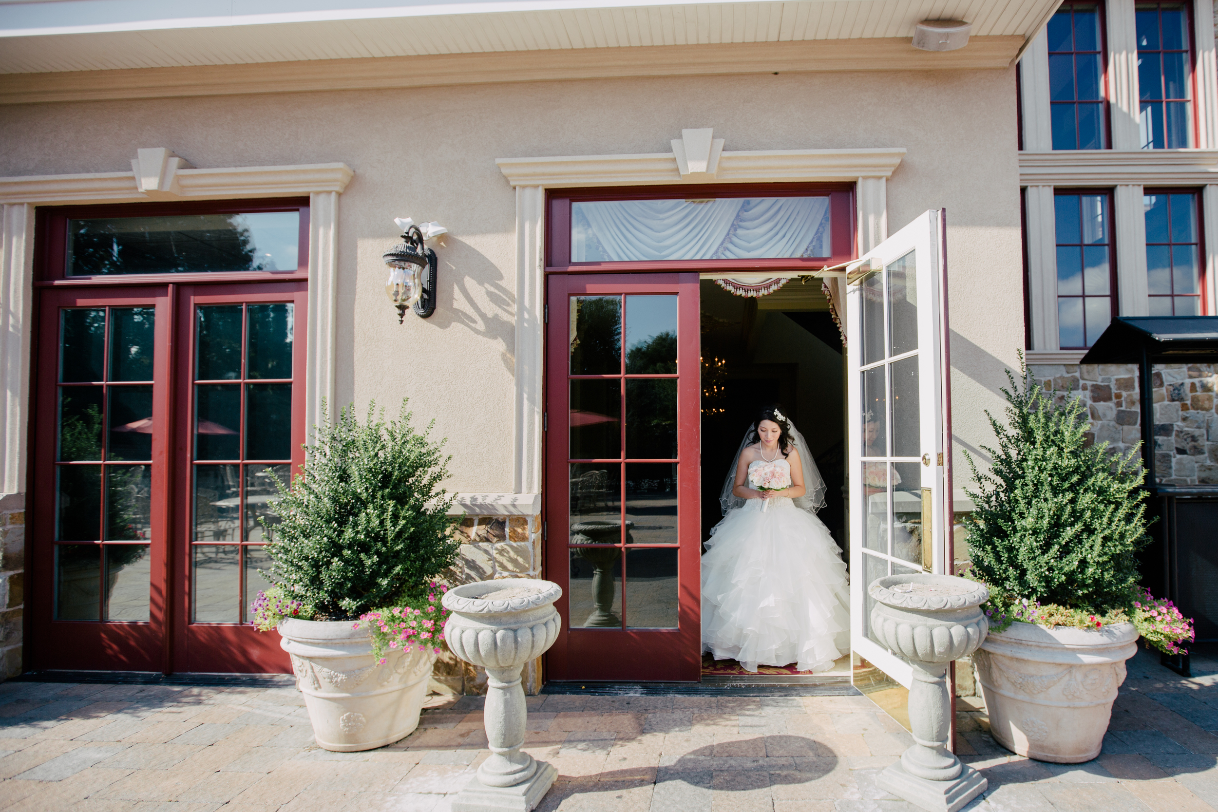 bride coming out the doors to go to the ceremony in queens