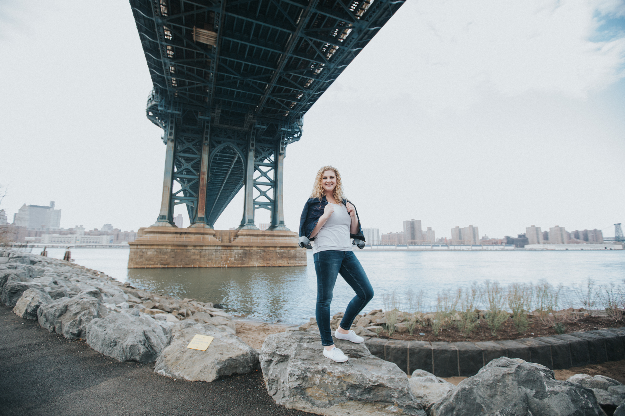 blonde girl standing under manhattan bridge