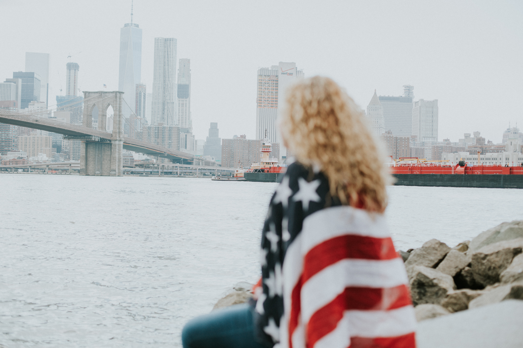 girl with American flag and city skyline