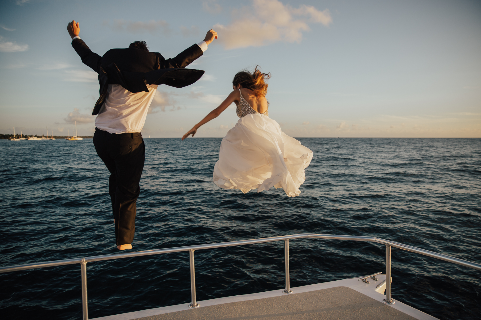 bride and groom jumping in the water