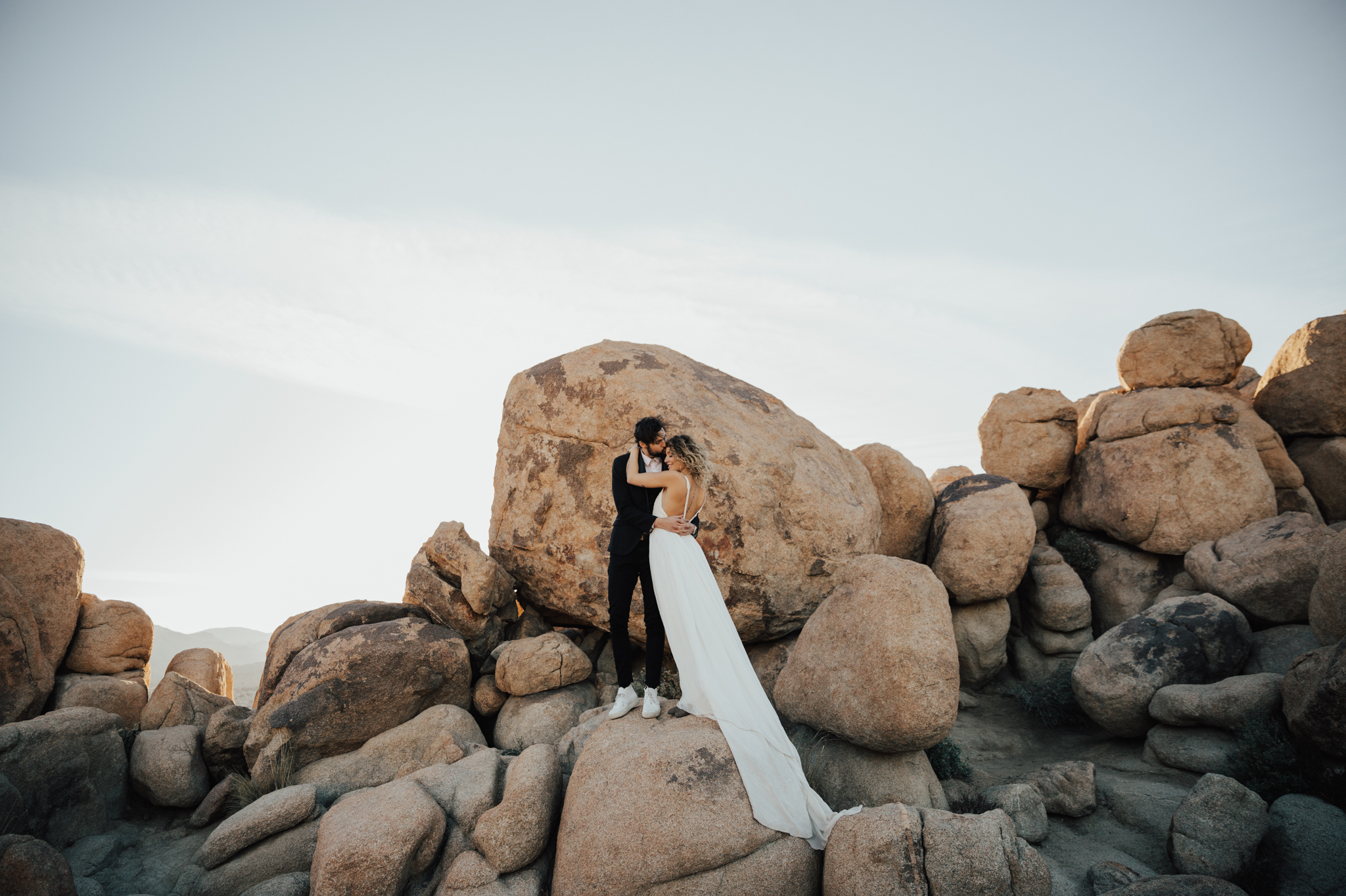 Couple standing on huge rock in Joshua tree
