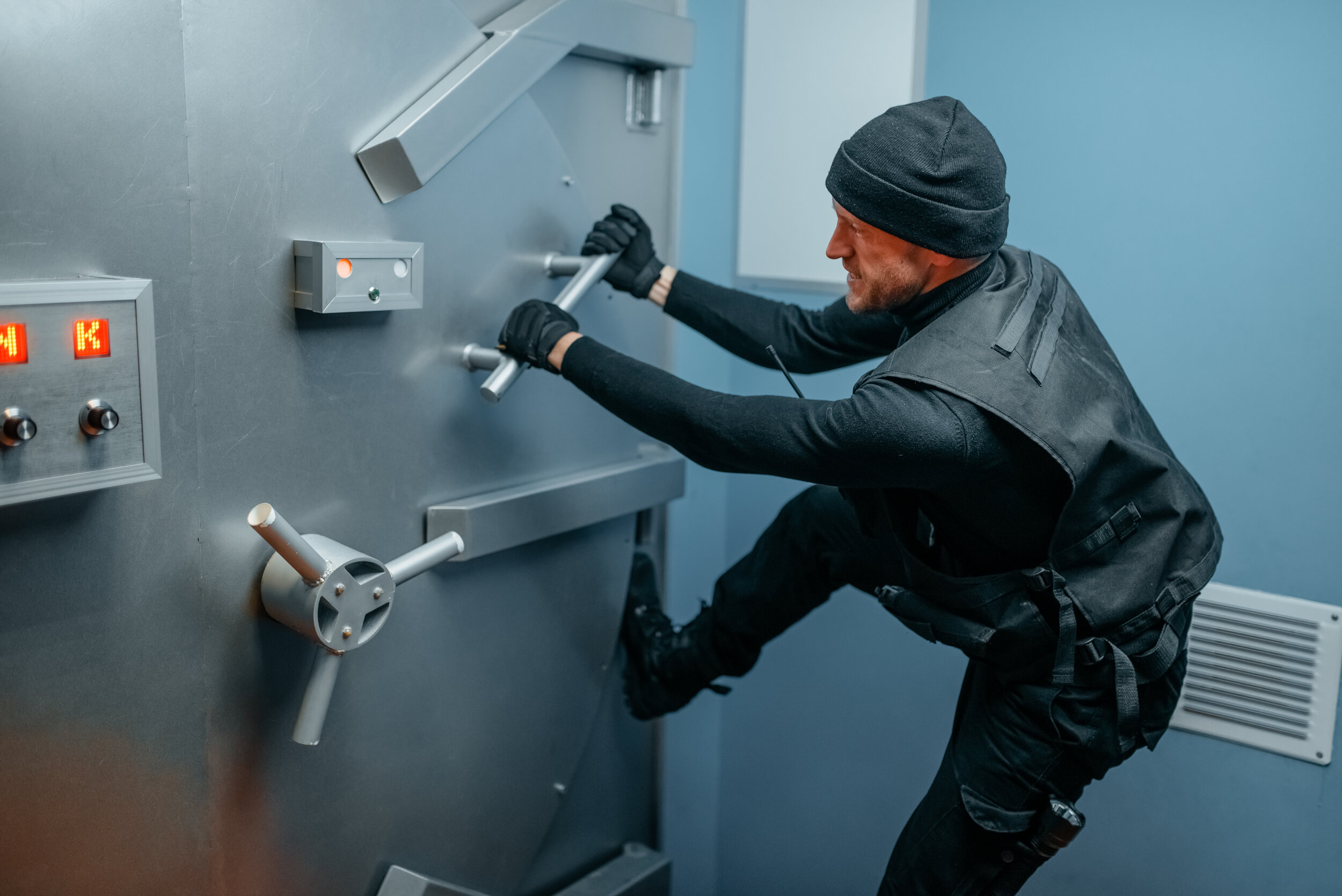Robber in black uniform trying to break vault lock