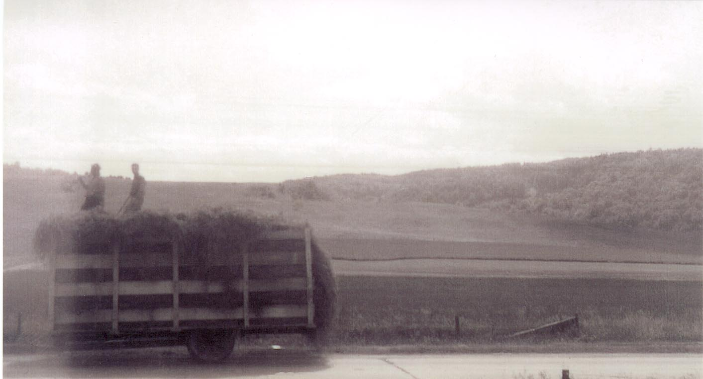 A truck moves hay down West Main St (Rt. 2) towards the barn. This photo was taken before imminent domain bisected the farm for the development of Interstate 89.