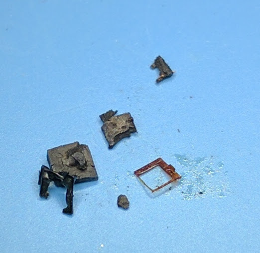 The remains after removing the die. The square metal piece is not the metalization ring mentioned below, but rather was surrounding the die.