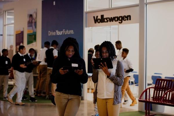 Two students from D.C. Public Schools stop to adjust their monthly budget outside the JA Finance Park Fairfax County Transportation Storefront where they applied for a car loan and chose a vehicle.