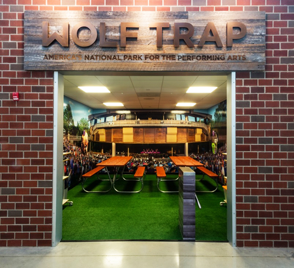 """Wolf Trap's storefront at JA Finance Park is just like stepping foot onto the grounds of Wolf Trap National Park for the Performing Arts, offering students a panoramic look at the Filene Center, with wooden picnic tables, a """"lawn,"""" and interactive exhibits that give youth a deeper look into the arts and entertainment options available to them at Wolf Trap."""