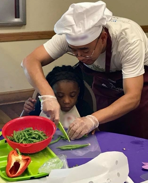 JUNE 2018, LI ZHU ASSISTS A STUDENTS WITH CUTTING STRING BEANS AT A COOKING LESSON PRESENTED BY HILLSBOROUGH SOCIAL SERVICES & JUNIOR CHEFS OF AMERICA AT THE OAKS AT RIVERVIEW COMMUNITY CENTER.