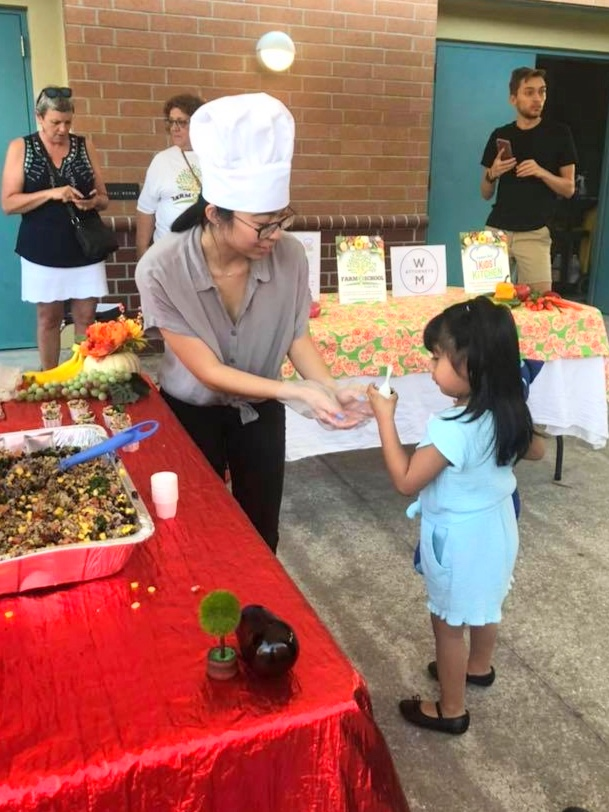 Febuary 2019: Kids Kitchen volunteer Kassidy Lee shares a quinoa black bean dish with a Muller Elementary student.