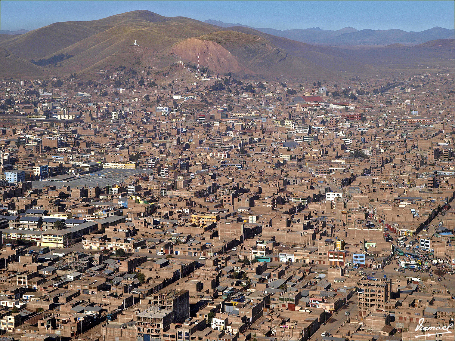 Aerial view of the city of Juliaca. Notice the brick color and metal frames that show the unfinished nature of most buildings. Photo credit: Panoramio