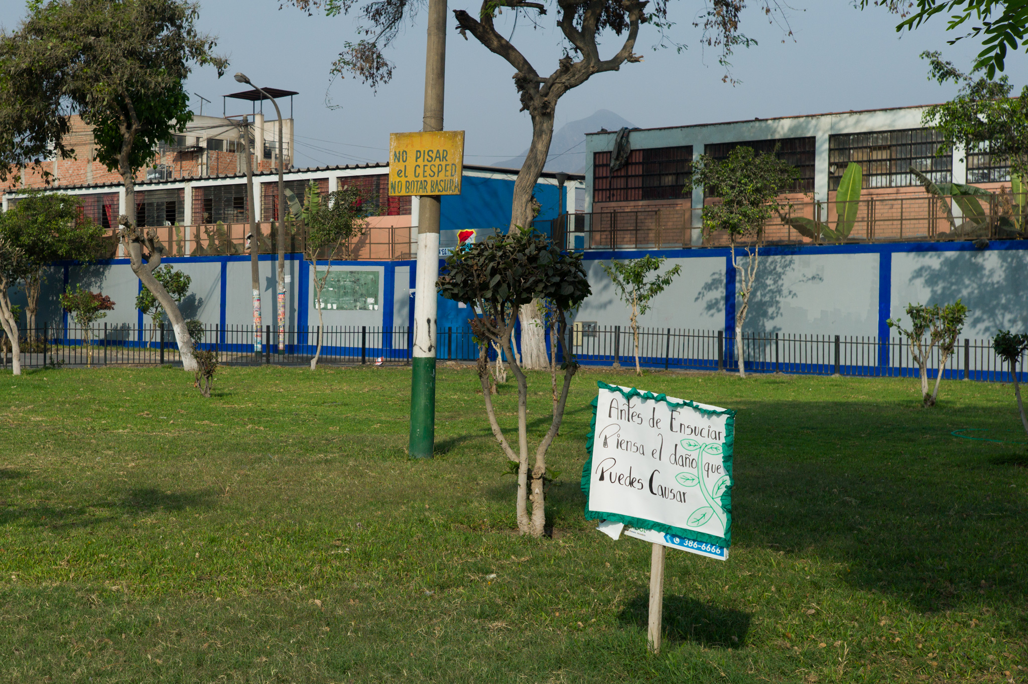 """Another fenced park. The white sign reads """"before making a mess, think of the damage you might cause."""""""