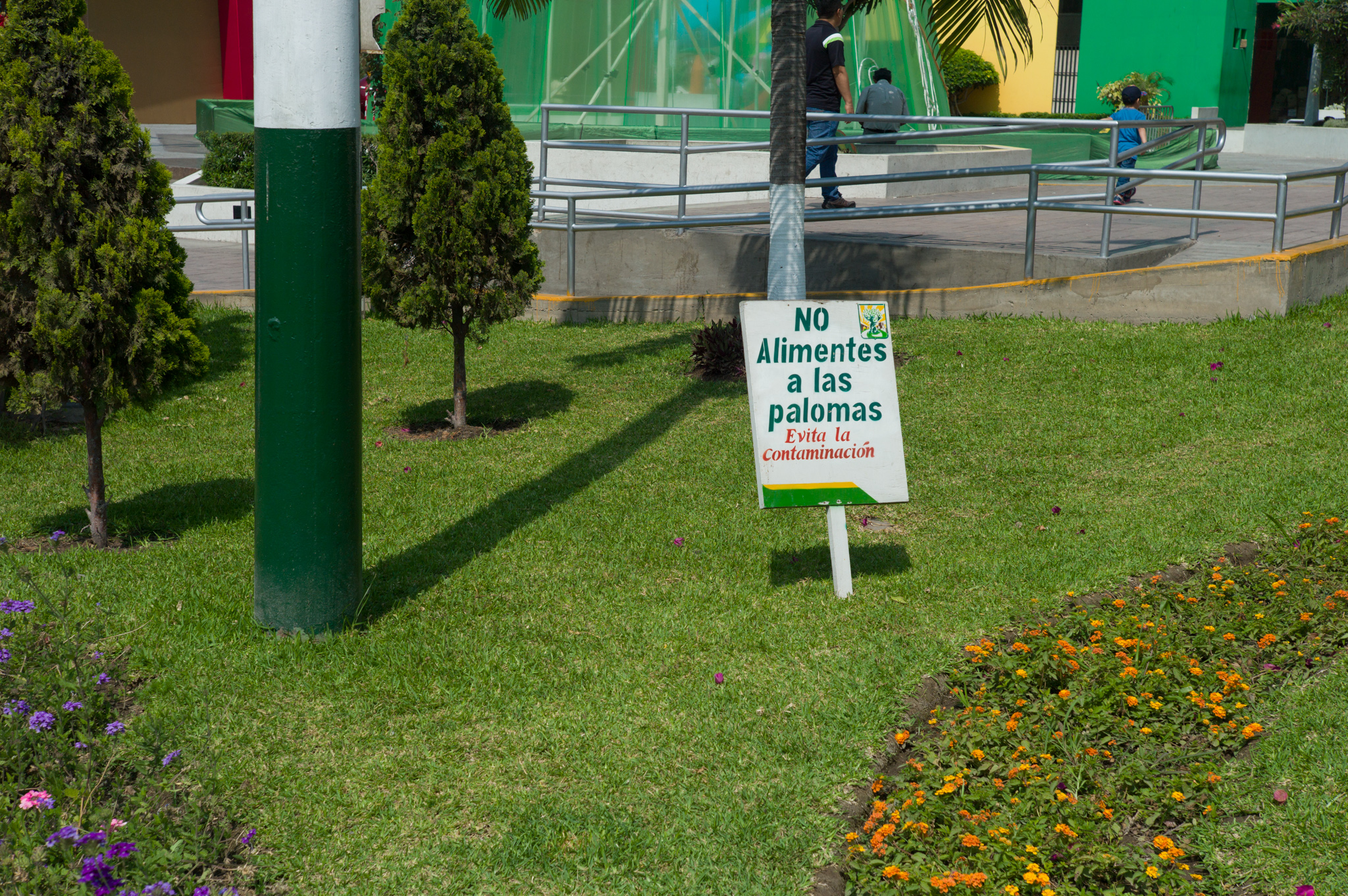 """Main district plaza, adjacent to Los Olivos's municipality. Sign reads """"do not feed the pigeons. Avoid polluting."""""""